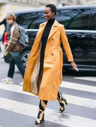 PARIS, FRANCE - FEBRUARY 28: A model wears an orange long trench coat, a black turtleneck pullover, beige and black zebra print pattern pointy boots, outside Ralph & Russo, during Paris Fashion Week - Womenswear Fall/Winter 2020/2021, on February 28, 2020 in Paris, France. (Photo by Edward Berthelot/Getty Images)