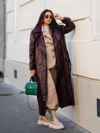 PARIS, FRANCE - DECEMBER 15: Gabriella Berdugo wears  sunglasses, a white turtleneck pullover, earrings, a necklace, a bi color beige and brown oversized blazer jacket and suit pants from Salisa NYC, beige nude biker platform shiny boots from AGL, a leather vynil aubergine-colored / purple trench coat from Maison Natan, a green quilted leather Chanel bag, on December 15, 2020 in Paris, France. (Photo by Edward Berthelot/Getty Images)