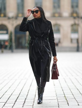 PARIS, FRANCE - DECEMBER 31: Emilie Joseph wears sunglasses from Gentle Monster, a black turtleneck pullover from Uniqlo, a black shiny liquid vinyl trench coat from Topshop, a burgundy leather Saint Laurent bag, tights, black shiny leather pointy ankle boots with high heels from By Far, on December 31, 2020 in Paris, France. (Photo by Edward Berthelot/Getty Images)