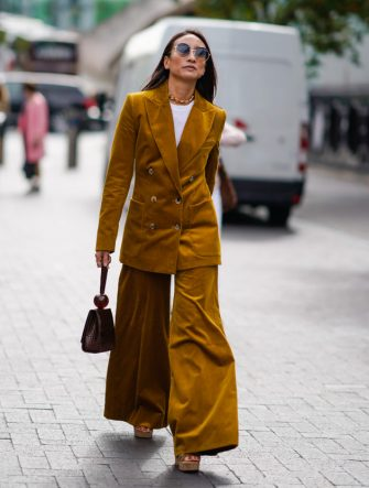 A guest wears an orange blazer jacket, orange flare pants, during London Fashion Week September 2018 on September 16, 2018 in London, England. (Photo by Edward Berthelot/Getty Images)
