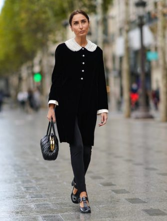 PARIS, FRANCE - OCTOBER 06: Geraldine Boublil wears a black jacket with buttons and white ruffled large collar, a black leather bag from Miu Miu, black pants, black leather shoes, outside Miu Miu, during Paris Fashion Week - Womenswear Spring Summer 2021, on October 06, 2020 in Paris, France. (Photo by Edward Berthelot/Getty Images)