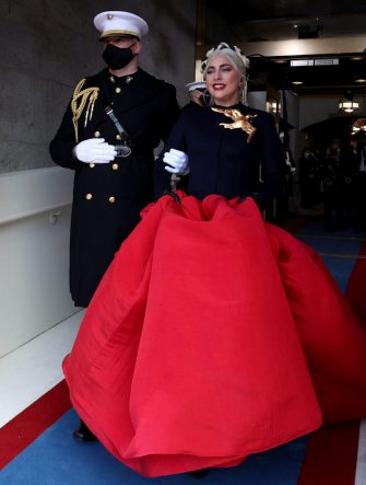 """WASHINGTON, DC - JANUARY 20: Singer Lady Gaga is escorted by Marine Capt. Evan Campbell as she arrives to perform """"The Star-Spangled Banner"""" at the inauguration of U.S. President-elect Joe Biden on the West Front of the U.S. Capitol on January 20, 2021 in Washington, DC.  During today's inauguration ceremony Joe Biden becomes the 46th president of the United States. (Photo by Jonathan Ernst-Pool/Getty Images)"""