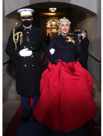 WASHINGTON, DC - JANUARY 20: Lady Gaga is escorted by U.S. Marine escort Capt. Evan Campbell to sing the National Anthem at the inauguration of U.S. President-elect Joe Biden on the West Front of the U.S. Capitol on January 20, 2021 in Washington, DC.  During todayâ  s inauguration ceremony Joe Biden becomes the 46th president of the United States. (Photo by Win McNamee/Getty Images)