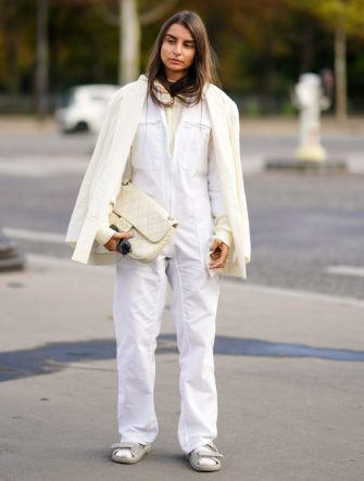 PARIS, FRANCE - OCTOBER 06: A guest wears a white jacket, a white jumpsuit, a white quilted Chanel bag, Chanel padded sandals, outside Chanel, during Paris Fashion Week - Womenswear Spring Summer 2021, on October 06, 2020 in Paris, France. (Photo by Edward Berthelot/Getty Images)
