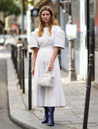 PARIS, FRANCE - OCTOBER 04: Natalia Verza wears a white pleated dress with puff shoulders, a white mesh woven leather bag, blue leather boots, outside Paco Rabanne, during Paris Fashion Week - Womenswear Spring Summer 2021, on October 04, 2020 in Paris, France. (Photo by Edward Berthelot/Getty Images)