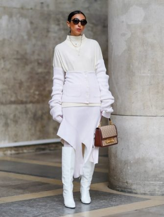 PARIS, FRANCE - OCTOBER 01: Gabriella Berdugo wears sunglasses, a total white and cream look made of a knit jumper with long gloves and white leather / vinyl heeled boots , printed monogram beige bag from Carolina Herrera, outside Chloe, during Paris Fashion Week - Womenswear Spring Summer 2021, on October 01, 2020 in Paris, France. (Photo by Edward Berthelot/Getty Images)