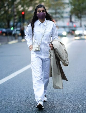 PARIS, FRANCE - OCTOBER 02: A guest wears a purple face mask, a white jumpsuit, a Jacquemus mini bag, holds a trench coat, outside Yohji Yamamoto, during Paris Fashion Week - Womenswear Spring Summer 2021, on October 02, 2020 in Paris, France. (Photo by Edward Berthelot/Getty Images)