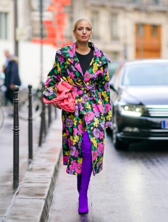 PARIS, FRANCE - FEBRUARY 25: Leonie Hanne wears earrings, a black top, a Givenchy pink bag, a Balenciaga trench coat with colorful flowers print, purple thigh-high sock-boots, during Paris Fashion Week - Womenswear Fall/Winter 2020/2021, on February 25, 2020 in Paris, France. (Photo by Edward Berthelot/Getty Images)