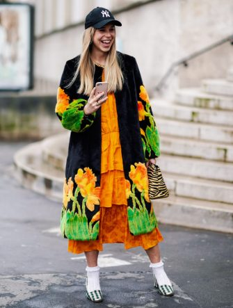 PARIS, FRANCE - FEBRUARY 28: A guest wears a NY black cap, a black fluffy coat with yellow,orange and green daffodils design, an orange dress, a beige and black zebra pattern bag, white openwork socks, deep green and white gingham slingback pumps, outside Atlein, during Paris Fashion Week Womenswear Fall/Winter 2019/2020, on February 28, 2019 in Paris, France. (Photo by Edward Berthelot/Getty Images)