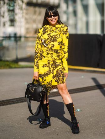 PARIS, FRANCE - JUNE 30: Susanna Lau wears sunglasses, a yellow dress with printed black flowers, a leather bag, boots, outside Acne, during Paris Fashion Week - Haute Couture Fall/Winter 2019/2020, on June 30, 2019 in Paris, France. (Photo by Edward Berthelot/Getty Images)