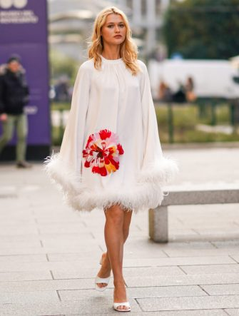 MILAN, ITALY - FEBRUARY 20: Chloe Lecareux wears a white dress with embroidered red/pink flower and fluffy parts, white shoes, outside Vivetta, during Milan Fashion Week Fall/Winter 2020-2021 on February 20, 2020 in Milan, Italy. (Photo by Edward Berthelot/Getty Images)