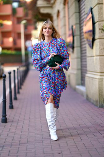 MILAN, ITALY - FEBRUARY 21: Jeanette Madsen wears a multicolor floral print dress, a green bag, a belt, white high boots, outside Marni, during Milan Fashion Week Fall/Winter 2020-2021 on February 21, 2020 in Milan, Italy. (Photo by Edward Berthelot/Getty Images)