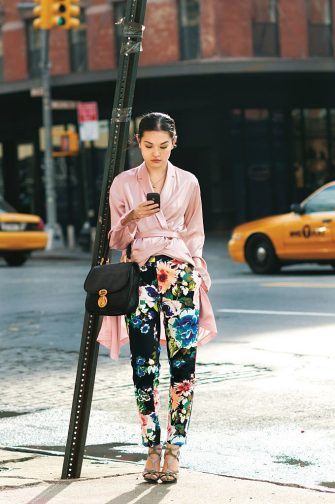 Jennifer Yee of Allure, wearing H&M floral pants with YSL coin necklace, La Perla pink silk robe, Balenciaga bag and Balenciaga snakeskin heels. (Photo byCitizen Couture/Condé Nast via Getty Images)