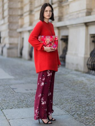 BERLIN, GERMANY - AUGUST 17: Maria Barteczko wearing red oversized wool sweater The Row, flared floral trousers Valentino, black heels Gianvito Rossi, red GG Marmont flower printed bag Gucci, round golden glasses Ray Ban on August 17, 2017 in Berlin, Germany. (Photo by Christian Vierig/Getty Images)