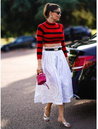 PARIS, FRANCE - JUNE 29: Laetitia Casta wears large earrings, sunglasses, a red and black cropped bare belly top, a belt, a white skirt with embroidery, a pink bag, silver shoes, outside Miu Miu Club 2020,  on June 29, 2019 in Paris, France. (Photo by Edward Berthelot/Getty Images)