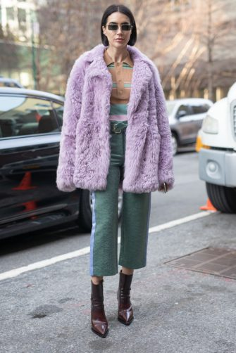 NEW YORK, NEW YORK - FEBRUARY 10: A guest is seen on the street during New York Fashion Week AW19 wearing purple fur coat, sea green pants on February 10, 2019 in New York City. (Photo by Matthew Sperzel/Getty Images)
