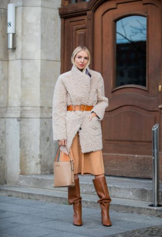 BERLIN, GERMANY - JANUARY 14: Leonie Hanne wearing total look Marc Cain: beige teddy coat, orange brown belt, pleated skirt, brown boots and bucket bag seen during the Berlin Fashion Week Autumn/Winter 2020 on January 14, 2020 in Berlin, Germany. (Photo by Christian Vierig/Getty Images)