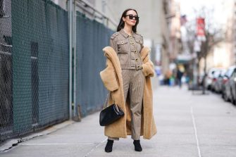 NEW YORK, NEW YORK - FEBRUARY 09: A guest wears a brown fluffy long coat, a gray jacket with golden large buttons, pants, black pointy shoes, a leather bag, sunglasses, outside Tory Burch, during New York Fashion Week Fall Winter 2020, on February 09, 2020 in New York City. (Photo by Edward Berthelot/Getty Images)