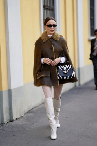 MILAN, ITALY - FEBRUARY 21: Mary Leest wears sunglasses, a brown leather aviator jacket with wool fluffy inner lining, a zebra black and white bag, Gucci tights, white high leather boots, outside Tod's, during Milan Fashion Week Fall/Winter 2020-2021 on February 21, 2020 in Milan, Italy. (Photo by Edward Berthelot/Getty Images)
