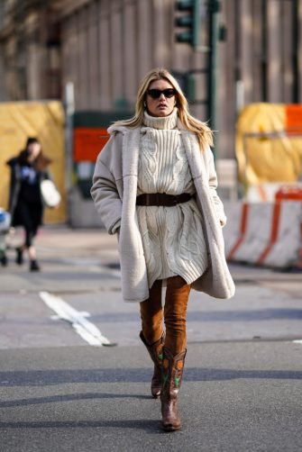 NEW YORK, NEW YORK - FEBRUARY 09: A guest wears sunglasses, a white wool knitted pullover, a belt, a fluffy coat, brown suede pants, brown leather floral print cowboy boots, outside Sies Marjan, during New York Fashion Week Fall Winter 2020, on February 09, 2020 in New York City. (Photo by Edward Berthelot/Getty Images)