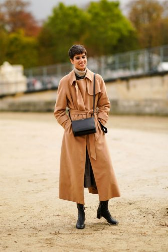 PARIS, FRANCE - SEPTEMBER 29: A model wears a brown trench coat, a wool turtleneck pullover, a black leather bag, black leather boots, outside Dior, during Paris Fashion Week - Womenswear Spring Summer 2021 on September 29, 2020 in Paris, France. (Photo by Edward Berthelot/Getty Images)