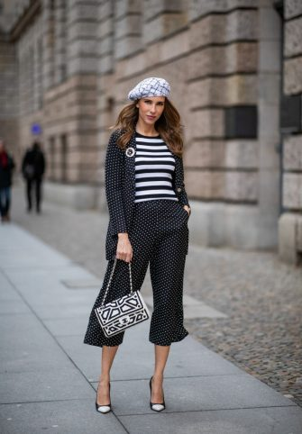 BERLIN, GERMANY - JANUARY 16:  Alexandra Lapp is seen wearing a long black blazer with dots and matching culotte pants, black and white striped sweater with a yellow detail from Steffen Schraut, a black and white tweed beret from the Chanel La Pausa collection, a black and white 2.55 flap bag from Chanel during the Berlin Fashion Week Autumn/Winter 2019 on January 16, 2019 in Berlin, Germany. (Photo by Christian Vierig/Getty Images)