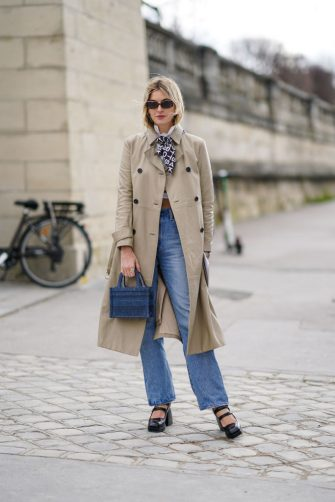 PARIS, FRANCE - FEBRUARY 25: Camille Charriere wears sunglasses, a trench coat, blue denim jeans pants, a Dior blue mini shopping bag, black shoes, a scarf, outside Dior, during Paris Fashion Week - Womenswear Fall/Winter 2020/2021, on February 25, 2020 in Paris, France. (Photo by Edward Berthelot/Getty Images)