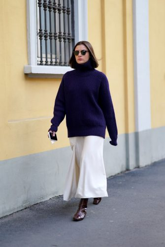 MILAN, ITALY - FEBRUARY 21: A guest wears sunglasses, a blue oversized pullover, a white skirt, brown leather boots, outside Tod's, during Milan Fashion Week Fall/Winter 2020-2021 on February 21, 2020 in Milan, Italy. (Photo by Edward Berthelot/Getty Images)