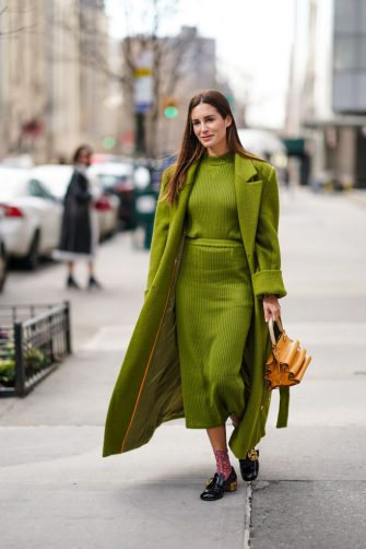 NEW YORK, NEW YORK - FEBRUARY 09: Gala Gonzalez wears a green long fluffy coat, a wool striped dress, an orange bag, floral print socks, black leather shoes, outside Tory Burch, during New York Fashion Week Fall Winter 2020, on February 09, 2020 in New York City. (Photo by Edward Berthelot/Getty Images)