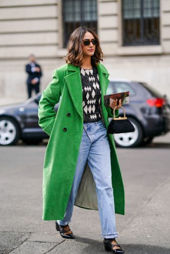 PARIS, FRANCE - SEPTEMBER 28: A guest wears sunglasses, a green corduroy long coat, a black and white geometric pattern print pullover, blue denim jeans pants, black leather pointy shoes, a bag, outside Elie Saab, during Paris Fashion Week - Womenswear Spring Summer 2020, on September 28, 2019 in Paris, France. (Photo by Edward Berthelot/Getty Images)