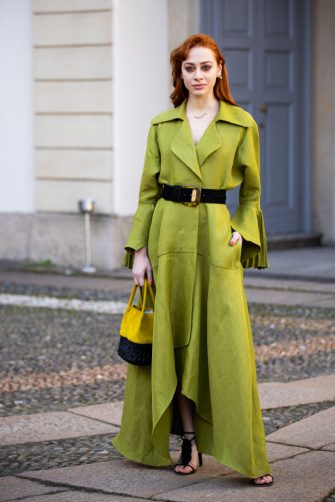 MILAN, ITALY - FEBRUARY 20: A guest, wearing a green long jacket, black belt, black heels and yellow and black bag, is seen outside Luisa Beccaria show, during Milan Fashion Week Fall/Winter 2020-2021 on February 20, 2020 in Milan, Italy. (Photo by Claudio Lavenia/Getty Images)