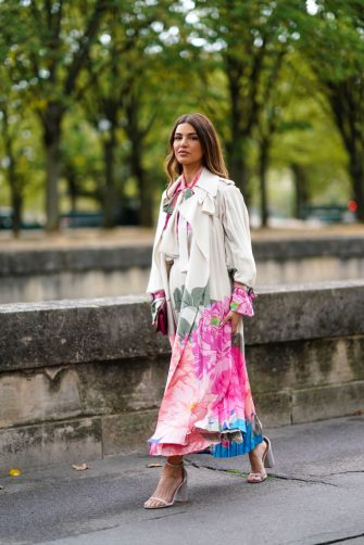 PARIS, FRANCE - SEPTEMBER 29: Negin Mirsalehi wears a pink, green and blue floral print cream-color top with a lavaliere, a pink, green and blue floral print cream-color pleated skirt, a cream-color trench-coat with pink, green and blue floral print lower part and cuffs, a clutch, taupe -color ankle-strap heeled sandals, outside Valentino, during Paris Fashion Week - Womenswear Spring Summer 2020, on September 29, 2019 in Paris, France. (Photo by Edward Berthelot/Getty Images)