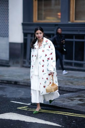 LONDON, ENGLAND - FEBRUARY 18: Bettina Looney wears earrings, a white floral print coat, a white frilly dress, a rectangular box bag, green suede mules, during London Fashion Week February 2019 on February 18, 2019 in London, England. (Photo by Edward Berthelot/Getty Images)