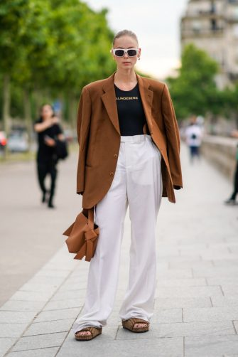 PARIS, FRANCE - JUNE 23: A guest wears white sunglasses, an oversized brown blazer jacket, a black t-shirt, white flare pants, sandals, outside Celine, during Paris Fashion Week - Menswear Spring/Summer 2020, on June 23, 2019 in Paris, France. (Photo by Edward Berthelot/Getty Images)