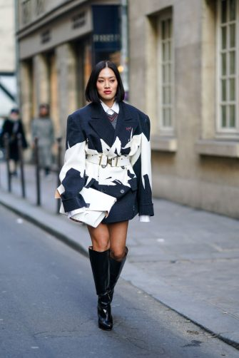 PARIS, FRANCE - JANUARY 22: Tiffany Hsu wears a dark blue and white oversized jacket/dress, a white belt, a white clutch, black thigh high boots, outside Maison Margiela, during Paris Fashion Week - Haute Couture Spring/Summer 2020, on January 22, 2020 in Paris, France. (Photo by Edward Berthelot/Getty Images )