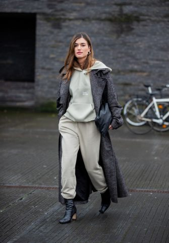COPENHAGEN, DENMARK - JANUARY 28: A guest is seen wearing hoody, jogger pants, grey coat outside 7 Days on Day 1 during Copenhagen Fashion Week Autumn/Winter 2020 on January 28, 2020 in Copenhagen, Denmark. (Photo by Christian Vierig/Getty Images)