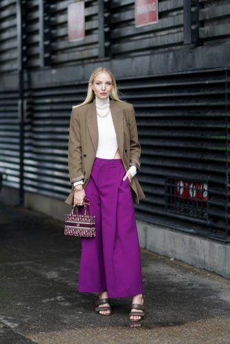 LONDON, ENGLAND - FEBRUARY 16: Leonie Hanne wears a white turtleneck pullover, a necklace, an oversized brown blazer jacket, a Dior mini tote bag, purple large flared pants, sandals, during London Fashion Week Fall Winter 2020 on February 16, 2020 in London, England. (Photo by Edward Berthelot/Getty Images)