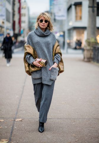 DUESSELDORF, GERMANY - DECEMBER 07: Gitta Banko wearing a grey, oversize knit turtleneck sweater with fake fur pockets by Zara, grey cotton-wool-mix flared trousers with button details on the ankles by Theory, green, oversize turn over scarf with golden pattern by BLONDWALK 4 a cuckoo moment capsule collection, gold clutch with star decor by a cuckoo moment, rose gold ring with green stingray leather by a cuckoo moment, black tubular nappa leather ankle boots by Yeezy, and golden Ray Ban Round Metal sunglasses on December 7, 2017 in Hamburg, Germany. (Photo by Christian Vierig/Getty Images)