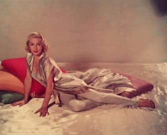 circa 1955:  A portrait of actor Lana Turner (1921 - 1995) posing on a silk sheet with large cushions in a sleeveless v-neck jumpsuit and a short-sleeved silk robe.  (Photo by Hulton Archive/Getty Images)