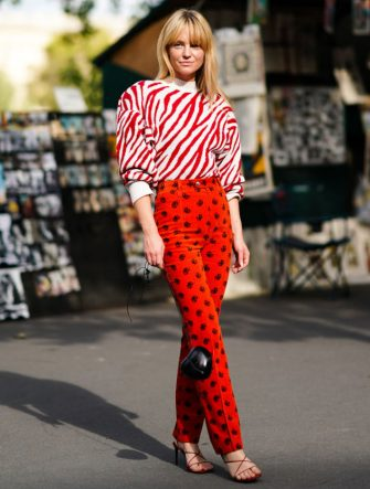 PARIS, FRANCE - SEPTEMBER 30: Jeanette Madsen wears a red and white striped zebra pattern print pullover with shoulder pads, red pants with printed features, a black bag shaped as a heart, shoes, outside Beautiful People, during Paris Fashion Week - Womenswear Spring Summer 2020, on September 30, 2019 in Paris, France. (Photo by Edward Berthelot/Getty Images)