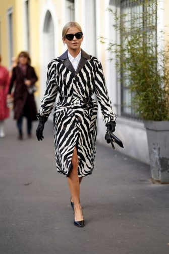 MILAN, ITALY - FEBRUARY 21: Caroline Daur wears sunglasses, a balck and white zebra pattern printed long coat, black leather gloves, black shoes, outside Tod's, during Milan Fashion Week Fall/Winter 2020-2021 on February 21, 2020 in Milan, Italy. (Photo by Edward Berthelot/Getty Images)