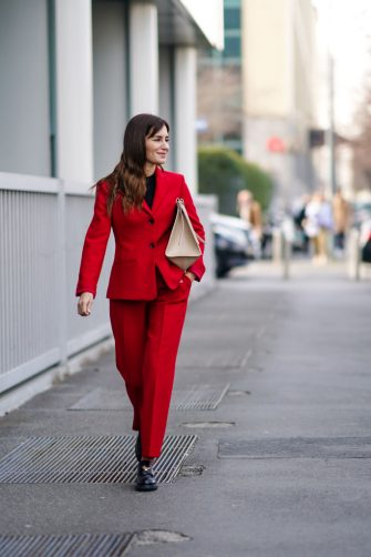 MILAN, ITALY - FEBRUARY 23: Gala Gonzalez wears a black top, a red blazer jacket, a cream color bag, red pants, black leather shoes, outside BOSS, during Milan Fashion Week Fall/Winter 2020-2021 on February 23, 2020 in Milan, Italy. (Photo by Edward Berthelot/Getty Images)
