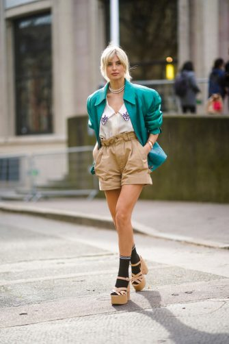 PARIS, FRANCE - MARCH 03: Xenia Adonts wears a green leather jacket with shoulder pads, a low neck shirt with printed flowers on the collar, pale brown shorts, black socks, platform shoes, a necklace, outside Miu Miu, during Paris Fashion Week - Womenswear Fall/Winter 2020/2021 on March 03, 2020 in Paris, France. (Photo by Edward Berthelot/Getty Images)