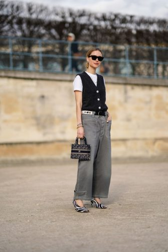 PARIS, FRANCE - FEBRUARY 25: Pernille Teisbaek wears sunglasses, a white t-shirt, a navy blue vest, a mini Dior shopping bag, a belt, gray pants, black and white zebra print pointy shoes, outside Dior, during Paris Fashion Week - Womenswear Fall/Winter 2020/2021, on February 25, 2020 in Paris, France. (Photo by Edward Berthelot/Getty Images)