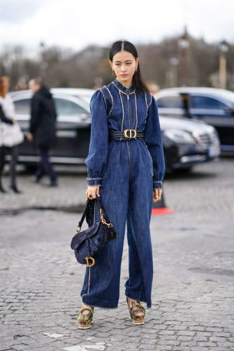 PARIS, FRANCE - FEBRUARY 25: Lala Takahashi  wears a blue denim jumpsuit, a Dior belt, a Dior Saddle bag, platform shoes, outside Dior, during Paris Fashion Week - Womenswear Fall/Winter 2020/2021, on February 25, 2020 in Paris, France. (Photo by Edward Berthelot/Getty Images)