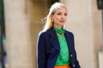 PARIS, FRANCE - JULY 12: Leonie Hanne wears golden earrings, a golden necklace, a dark navy blue Prada blazer jacket, a green ruffled silky Prada shirt with frilly collar, on July 12, 2020 in Paris, France. (Photo by Edward Berthelot/Getty Images)