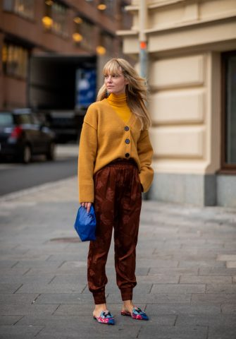 STOCKHOLM, SWEDEN - AUGUST 28:  Jeannette Madsen wearing mustard cardigan and turtleneck, jogger pants with print, blue clutch is seen during Stockholm Runway SS19 on August 28, 2018 in Stockholm, Sweden. (Photo by Christian Vierig/Getty Images)