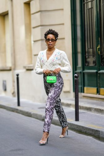 PARIS, FRANCE - AUGUST 26: Ellie Delphine wears pearl beaded hair pins, golden earrings, a golden chain necklace, a white wool floral print cropped cardigan from Alessandra Rich, a green studded Valentino bag, snake python print pants from the Attico, high heels shoes, on August 26, 2020 in Paris, France. (Photo by Edward Berthelot/Getty Images)