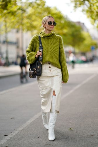 PARIS, FRANCE - SEPTEMBER 30: Leonie Hanne wears sunglasses, a green wool turtleneck knitted pullover, a Givenchy bag, white side slit skirt, white boots, outside Beautiful People, during Paris Fashion Week - Womenswear Spring Summer 2020, on September 30, 2019 in Paris, France. (Photo by Edward Berthelot/Getty Images)