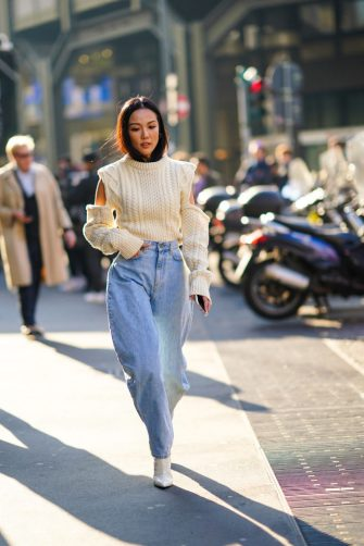 MILAN, ITALY - FEBRUARY 22: Yoyo Cao wears a white wool pullover, large pale blue denim pants, white boots, outside Philosophy, during Milan Fashion Week Fall/Winter 2020-2021 on February 22, 2020 in Milan, Italy. (Photo by Edward Berthelot/Getty Images)